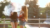 mod : Two women vaping outdoor. The evening sunset over the city. Toned image. Stock Footage