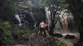 Мауи : Couple in love under a waterfall in a cave. A pair of lovers. Bali trip. Tropics. Journey. Aerial shot. Travel concept.