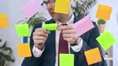 bem : handsome businessman in eyeglasses writing on colorful sticky notes