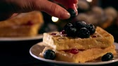 foco seletivo : slow motion of woman putting blueberry on belgian waffles in plate