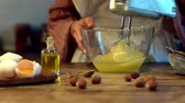 recept : female cook whipping eggs in glass bowl