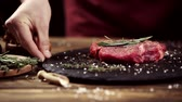 rozmarýna : Cropped view of man putting on table plate with raw meat steak decorated with spices and rosemary isolated on black