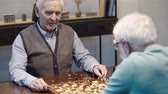 scacchi : senior man talking while playing chess with friend and pressing button on chess clock at table
