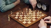cronometragem : partial view of two senior men playing chess and pressing button on chess clock at table Stock Footage
