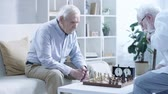 cronometragem : two pensive senior men playing chess and pressing button on chess clock at table in living room