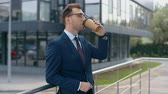 selective focus of businessman drinking coffee to go, smiling and looking at camera near building
