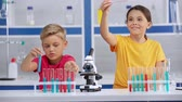 waterglas : Hyperlapse of kids mixing liquids in laboratory Stockvideo