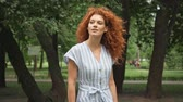 takje : selective focus of curly redhead woman walking in park