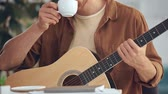 csészealj : cropped view of man playing acoustic guitar and drinking coffee