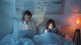 oso de peluche : mother using laptop while daughter using digital tablet in bed