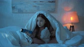 korku : scared child sitting on bed under blanket at night Stok Video
