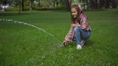 エレメンタリー : happy child playing with water stream on green lawn