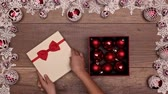 deslizamento : Hands opening christmas present revealing bunch of red xmas baubles - inside seasonal decorations frame, top view Stock Footage