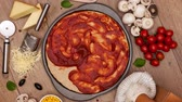 время приема пищи : Top view of making a pizza with ingredients appearing on the slowly rotating setting - stop motion animation, camera rotates and zooms in Стоковые видеозаписи