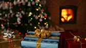 borítás : Many christmas gifts in front of fireplace and blurry lights on xmas tree in the evening - camera sliding Stock mozgókép