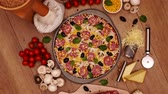 салями : Camera spin above a homemade delicious pizza in round pan with fresh ingredients around on the table - top view