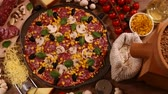 salame : Camera slide above homemade delicious pizza in round pan with fresh ingredients around on the table - wide view, slow move