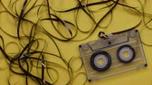 estéreo : Retro music cassette with tangled tape hanging outside, slowly withdrawing it
