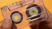 sztereó : Hand holding and reeling transparent compact audio cassette tape - on orange background, closeup Stock mozgókép