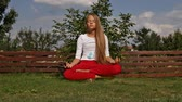 összhang : Young girl meditate in lotus position - hovering above grass in the garden, camera slide