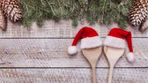Christmas hats on wooden spoons in holidays setting slide into frame - stop motion animation Stock Footage