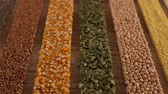 опции : Various seeds and grains arranged in colorful stripes on the table - camera slide, diverse diet concept