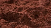Chocolate pieces fall into cocoa powder stirring up clouds of the delicious ingredient - close up, slow motion, camera slide
