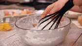 frusta : Woman hand whip thick foam of egg whites in a glass bowl with egg whisk - close-up, slow motion