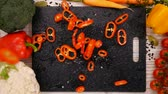 couve flor : Pepper slices falling on chopping board framed by fresh vegetables on the table - slow motion, top view