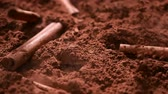 Cinnamon bars fall into cocoa powder stirring up clouds of sweet dust - close up, slow motion, camera slide