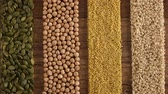 Various seeds and grains arranged in colorful stripes on the table - camera slide over, diverse diet background concept