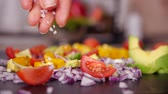 granulos : Woman hand adding large grain salt to vegetables mix prepared on the cutting board - closeup, slow motion of falling granules Archivo de Video