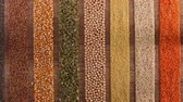 corn : Various seeds and grains arranged in colorful stripes on the table - top view, gluten free and diverse diet concept, slow camera slide