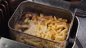 immerse : Shaking french fries in a wire basket then immerse them in boiling hot oil again - close up, static camera, top view, slow motion