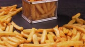 French fries served in a metallic mesh frying basket shaped recipient on slate plate - dark background, camera slide forward approaching and slowly tilt up