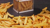 French fries served in a frying basket shaped recipient, hands taking pieces  - dark background, camera slide forward approaching and slowly tilt up Vídeos