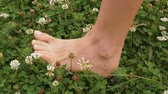 boso : Woman foot stepping on grass and other green vegetation - close up, slow motion