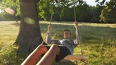 Young teenager boy swinging on rope swing outdoors - the end of childhood and the nostalgia of times past concept, slow motion