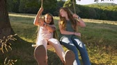 Two happy girls have fun smiling and swinging on rope swing outdoors - front view, camera in low angle rising, slow motion