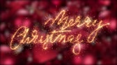 Merry christmas writing in sparkler twinkles appear over red xmas decorations background - rack focus to text