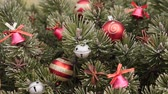 Close up of frosty pine branches decorated with christmas decorations. New year fir tree with xmas tree decorations. Holiday season background - sliding camera