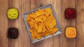 Tortilla chips filling a rotating rectangular plate with assorted sauces filling bowls on the side - stop motion animation