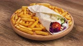 Making a kebab or gyros - a traditional sandwich wrapped in wheat wraps and various fresh ingredients - with a side of fried potato, side view of a rotating plate, stop motion animation