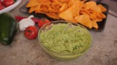 Hands scoop guacamole sauce with delicious tortilla chips - static camera 무비클립