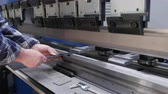Industrial metal sheet press brake machine operation - hands demonstrate metalworks with bending press machinery, close up, camera slide