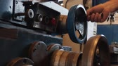 Male hand adjusting industrial machine rotating a wheel - close up, camera zoom out