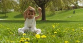 Cute baby girl playing with grass in park. Shot in 4K RAW on a cinema camera. Vídeos