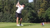 taşaklar : Young male golf player hitting the ball Stok Video