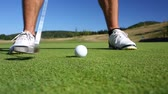 desafio : The Putting Green. Close-up view of a male golf player as she puts under-par on the Green.
