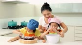 kitchen counter : Smiling mother and cute daughters baking together at home in the kitchen